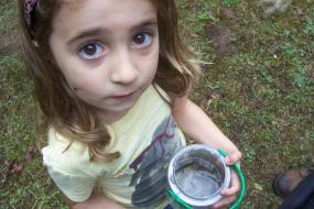 Young girl holding a bucket with a crayfish inside