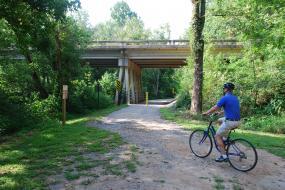 Biker on path leading under a roadway