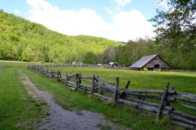 Trail running past split rail fence and barn