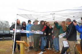 Ribbon cutting ceremony underneath pop up tent in a light rain