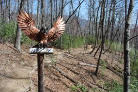 Wooden owl perched on a wooden trail marker
