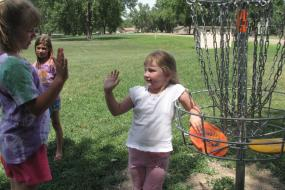 3 young girls hanging out by a disc golf basket