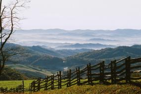 split rail fence in the foreground and rolling misty mountains in the background