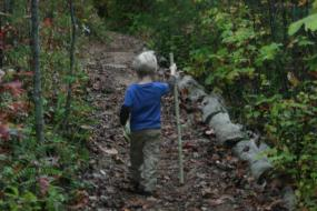 Young boy on trail with walking stick