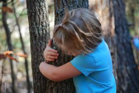 Young girl hugging a tree