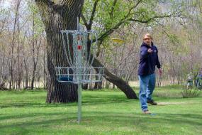 man throwing disc at disc golf basket