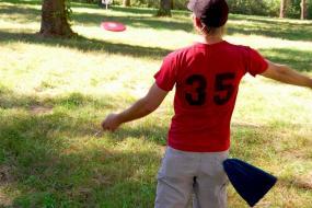 Disc golfer throwing toward a basket