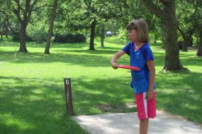 young girl preparing to throw a disc
