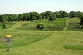view of the course and a disc golf basket in the foreground