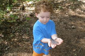 Young boy playing with feather on trail