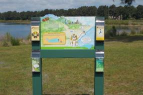 Trailhead sign with brochures in front of lake