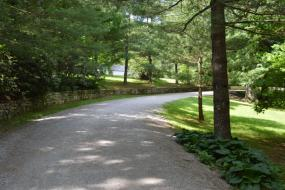 Gravel roadway bordered by a stacked stone wall