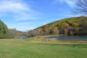 Two lakes in front of a wooded hill