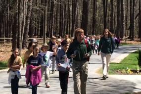 Group of kids hiking down a paved path
