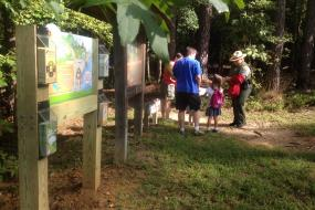 A family and the Kids in Parks trailhead sign
