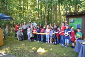 A group of kids cut the ribbon at the opening of the trail