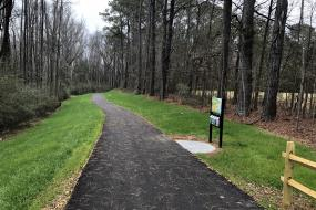A look down the Lindsay Pettus Greenway and the TRACK Trail trailhead sign.