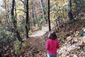 Young girl walking on  trail in fall