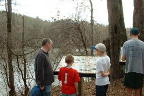 Family at interpretive sign along river