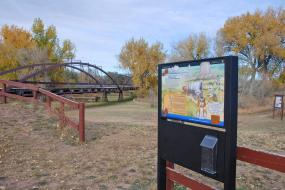 Fort Laramie TRACK Trailhead sign with iron bridge in the background