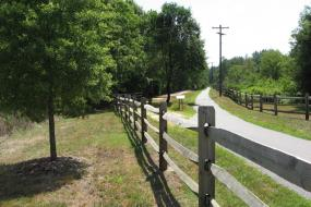 Split rail fence by paved trail