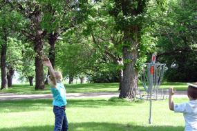 two children playing near the basket for hole 8