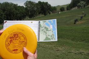 close up of someone holding a yellow disc with red writing and a scorecard