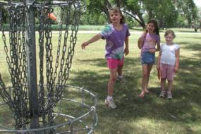 3 young girls near disc golf basket and one of them is throwing a disc at the basket
