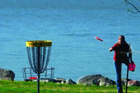 woman throwing a disc at the basket for hole 1